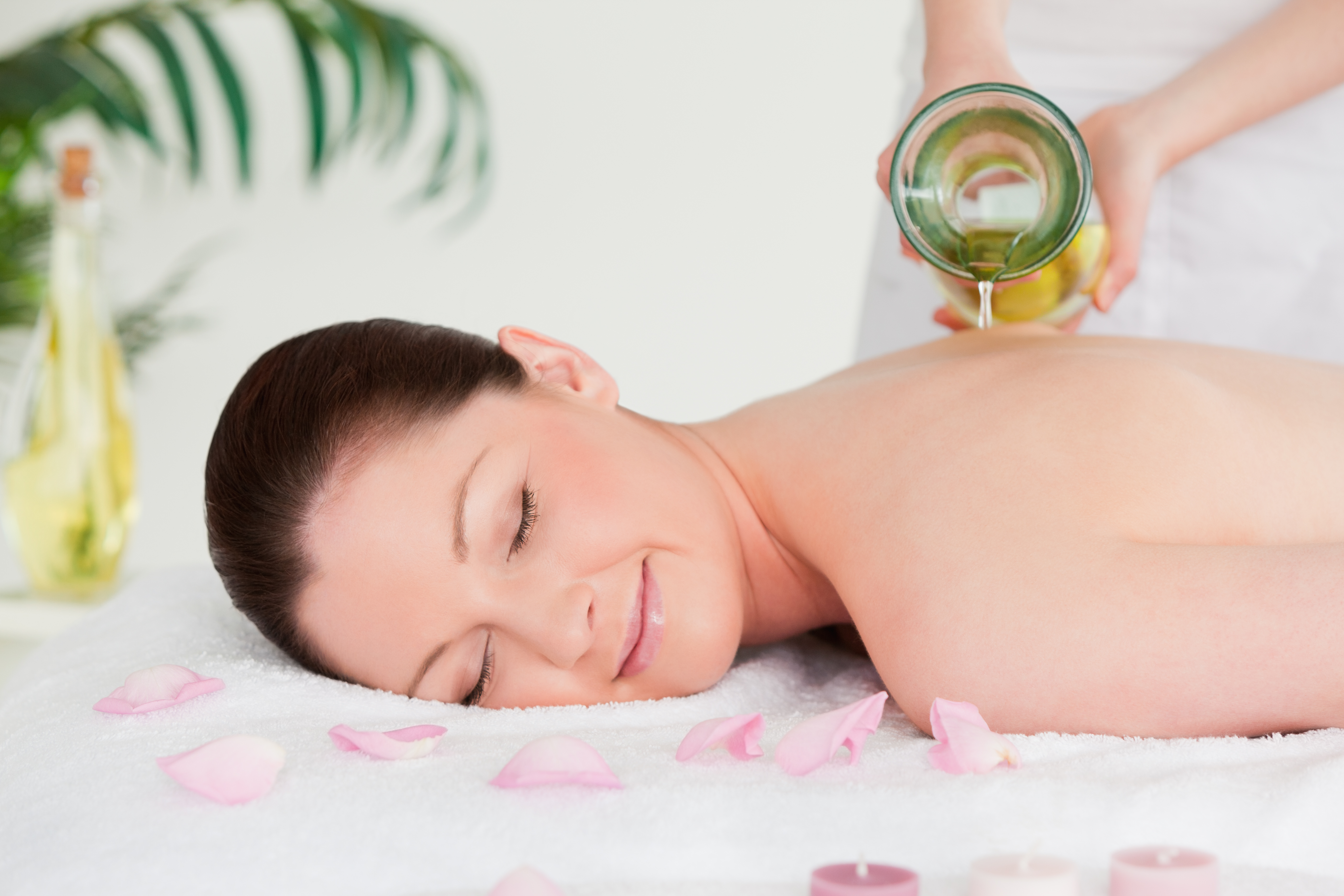 Masseuse pouring massage oil on a young woman's back in a spa